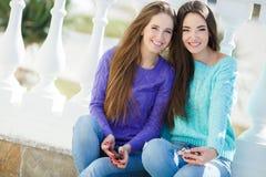 Dos muchachas que escuchan la música en sus smartphones Imagen de archivo libre de regalías