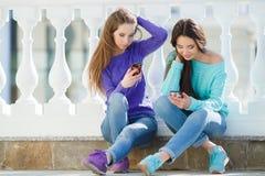 Dos muchachas que escuchan la música en sus smartphones Foto de archivo