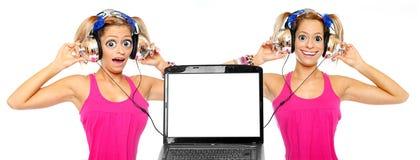 Dos muchachas que escuchan una música de la computadora portátil. Imágenes de archivo libres de regalías