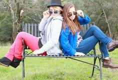 Dos muchachas que fijan en un banco Fotografía de archivo