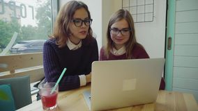 Dos muchachas que hablan con los amigos vía webchat o que tienen una charla video en café metrajes