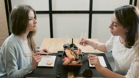 Dos muchachas que hablan durante cena en el restaurante almacen de video