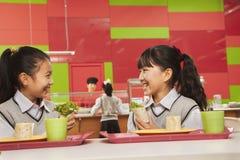 Dos muchachas que hablan en el almuerzo en cafetería de la escuela Foto de archivo libre de regalías