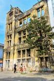 Dos muchachas que hablan en frot de un edificio alto abandonado en Jakar Imagen de archivo