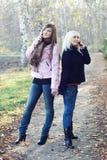 Dos muchachas que hablan en los teléfonos móviles Foto de archivo libre de regalías