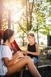 Dos muchachas que hablan en un patio en verano Foto de archivo