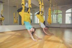 Dos muchachas que hacen deportes de la yoga de la mosca imágenes de archivo libres de regalías