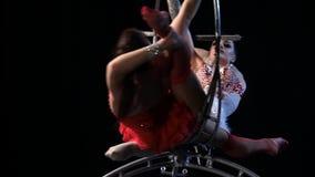 Dos muchachas que hacen girar en un aro en etapa Fondo negro Cámara lenta Cierre para arriba metrajes