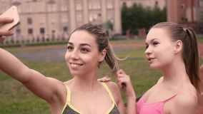 Dos muchachas que hacen muecas al tomar la foto con el teléfono Mujeres jovenes de la aptitud que presentan al tomar la foto en p almacen de metraje de vídeo