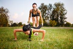 Dos muchachas que hacen pectorales Entrenamiento al aire libre Fotografía de archivo