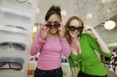 Dos muchachas que intentan en las gafas de sol en retrato del boutique Foto de archivo