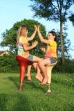 Dos muchachas que juegan al juego mientras que se sienta en sillas de la barra Fotografía de archivo libre de regalías