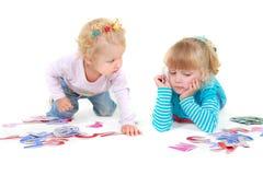 Dos muchachas que juegan con las cartas coloridas Imagen de archivo