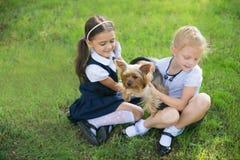 Dos muchachas que juegan con un perro foto de archivo libre de regalías