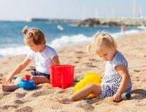 Dos muchachas que juegan en la playa Fotos de archivo