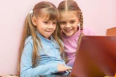 Dos muchachas que juegan en la risa de la diversión del cuaderno Foto de archivo