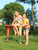Dos muchachas que juegan en sillas de la barra Fotos de archivo libres de regalías