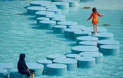 Dos muchachas que juegan en una piscina urbana en Kuala Lumpur foto de archivo