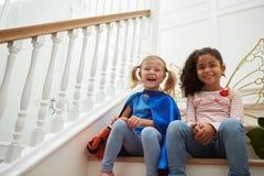 Dos muchachas que juegan vistiendo para arriba los juegos que se sientan en las escaleras Foto de archivo