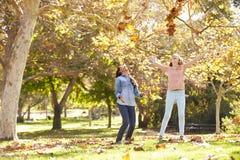 Dos muchachas que lanzan a Autumn Leaves In The Air Imagen de archivo libre de regalías