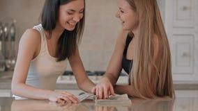 Dos muchachas que leen la revista de moda almacen de metraje de vídeo