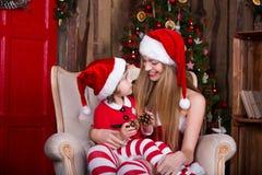 Dos muchachas que llevan el adornamiento del vestido y del sombrero de Navidad Imagenes de archivo
