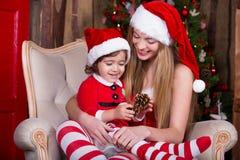 Dos muchachas que llevan el adornamiento del vestido y del sombrero de Navidad Imagen de archivo libre de regalías