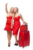 Dos muchachas que llevan rojo se visten con la fabricación grande de la maleta y del bolso imagen de archivo