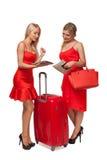 Dos muchachas que llevan rojo se visten con la maleta y bolso y tabl grandes fotografía de archivo libre de regalías