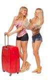 Dos muchachas que llevan vaqueros ponen en cortocircuito con el mapa y la maleta roja Fotos de archivo libres de regalías