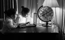Dos muchachas que mecanografían el email en el ordenador portátil en la noche Imagen de archivo
