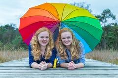 Dos muchachas que mienten en naturaleza debajo del paraguas colorido Imagen de archivo libre de regalías