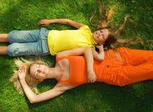 Dos muchachas que mienten en un prado Imagenes de archivo