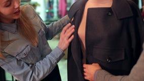 Dos muchachas que miran la ropa en un maniquí en tienda, ella elige una capa del otoño almacen de metraje de vídeo