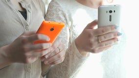 Dos muchachas que miran las fotos usando los teléfonos móviles almacen de video