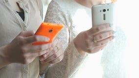 Dos muchachas que miran las fotos usando smartphones metrajes