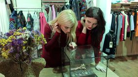 Dos muchachas que miran los accesorios y la joyería en el contador en una tienda de ropa almacen de video