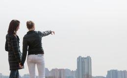 Dos muchachas que miran a un panorama de la ciudad Imagenes de archivo