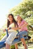 Dos muchachas que montan en el balancín en patio Fotos de archivo libres de regalías