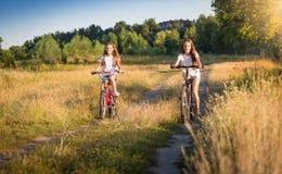 Dos muchachas que montan las bicicletas en prado en el día soleado Imagen de archivo libre de regalías