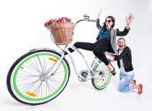 Dos muchachas que montan una bici que hace caras divertidas - en fondo azulado Imágenes de archivo libres de regalías