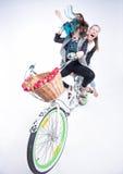 Dos muchachas que montan una bici que hace caras divertidas - en fondo azulado Fotos de archivo