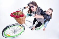 Dos muchachas que montan una bici que hace caras divertidas - en fondo azulado Fotos de archivo libres de regalías