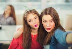 Dos muchachas que ponen mala cara mientras que toma una foto del selfie en el teléfono móvil Fotografía de archivo