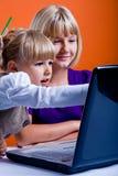 Dos muchachas que practican surf Internet Imágenes de archivo libres de regalías