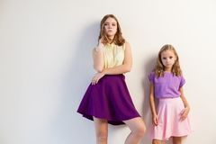 Dos muchachas que presentan con los vestidos de moda brillantes en un fondo blanco Imágenes de archivo libres de regalías