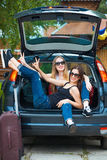 Dos muchachas que presentan en coche Fotos de archivo libres de regalías
