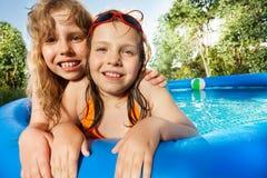 Dos muchachas que presentan en la piscina en el día soleado Foto de archivo libre de regalías