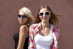 Dos muchachas que presentan en una pared marrón, los vidrios, blonde y morenita del fondo Foto de archivo libre de regalías