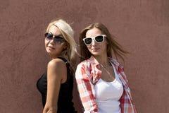 Dos muchachas que presentan en una pared marrón, los vidrios, blonde y morenita del fondo Foto de archivo
